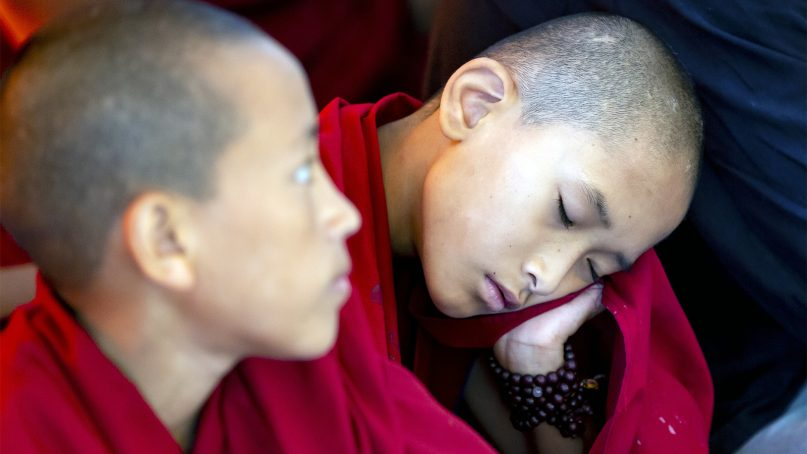 A novice monk sleeps during a talk by the Tibetan spiritual leader Dalai Lama at the Tsuglakhang temple in Dharmsala, India, on Sept. 4, 2019. The three-day talk, which was organized at the request of a Southeast Asian Buddhist group, ended Friday. (AP Photo/Ashwini Bhatia)