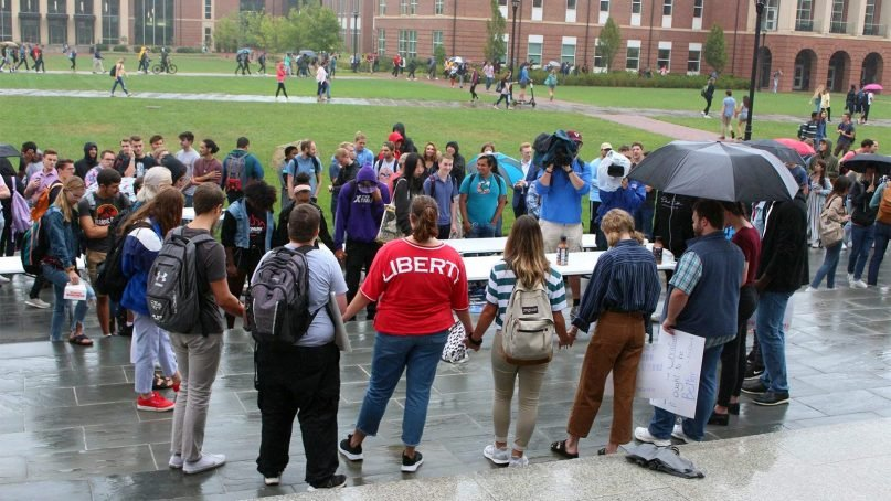 A circle of students hold hands during a demonstration at Liberty University on Sept. 13, 2019, in Lynchburg, Virginia. Demonstrating students want more transparency from school leadership, particularly President Jerry Falwell Jr. Photo courtesy of Austin Gaebe