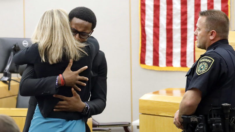 Botham Jean's younger brother Brandt Jean hugs convicted murderer and former Dallas Police Officer Amber Guyger after delivering his impact statement to her after she was sentenced to 10 years in jail, on Oct. 2, 2019, in Dallas. Guyger shot and killed Botham Jean, an unarmed 26-year-old neighbor in his own apartment last year. She told police she thought his apartment was her own and that he was an intruder. (Tom Fox/The Dallas Morning News via AP, Pool)