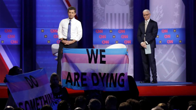 Democratic presidential candidate South Bend Mayor Pete Buttigieg, left, listens to protestors along with CNN moderator Anderson Cooper as he speaks during the Power of our Pride Town Hall on Oct. 10, 2019, in Los Angeles. The LGBTQ-focused town hall featured nine 2020 Democratic presidential candidates. (AP Photo/Marcio Jose Sanchez)