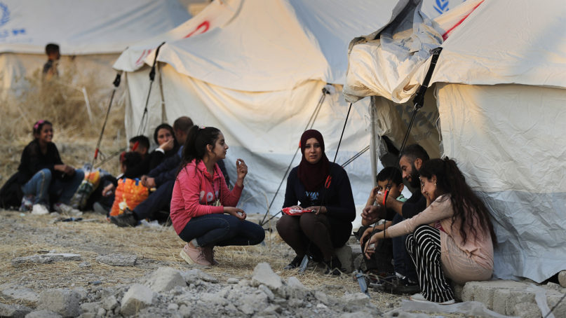 Syrians who were displaced by the Turkish military operation in northeastern Syria wait to receive tents and aid supplies at the Bardarash refugee camp, north of Mosul, Iraq, on Oct. 17, 2019. (AP Photo/Hussein Malla)