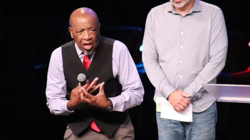 John Perkins, left, speaks at the Mosaix conference on Nov. 7, 2019, in Keller, Texas. Mark DeMyaz, president of Mosaix Global Network, stands behind Perkins on stage. RNS photo by Adelle M. Banks