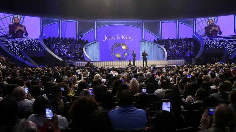 Kanye West, right, answers questions from senior pastor Joel Osteen, left, during the 11 a.m. service at Lakewood Church, Sunday, Nov. 17, 2019, in Houston. (AP Photo/Michael Wyke)