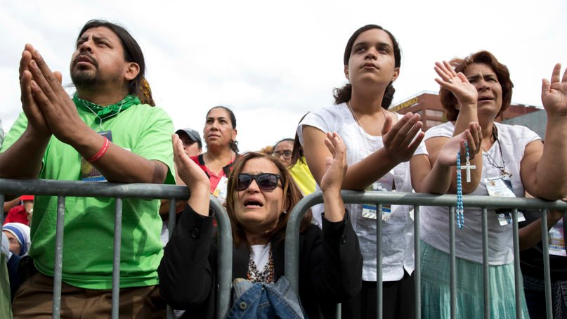 Milagros Orengo, second from left, her daughter Emily Orengo, and Maria Santos, right, all from Egg Harbor, N.J. pray behind a barricade at Independence Mall in Philadelphia, as a Mass with Pope Francis at the Cathedral Basilica of Sts. Peter and Paul is projected on a large screen, Saturday, Sept. 26, 2015. (AP Photo/Carolyn Kaster)