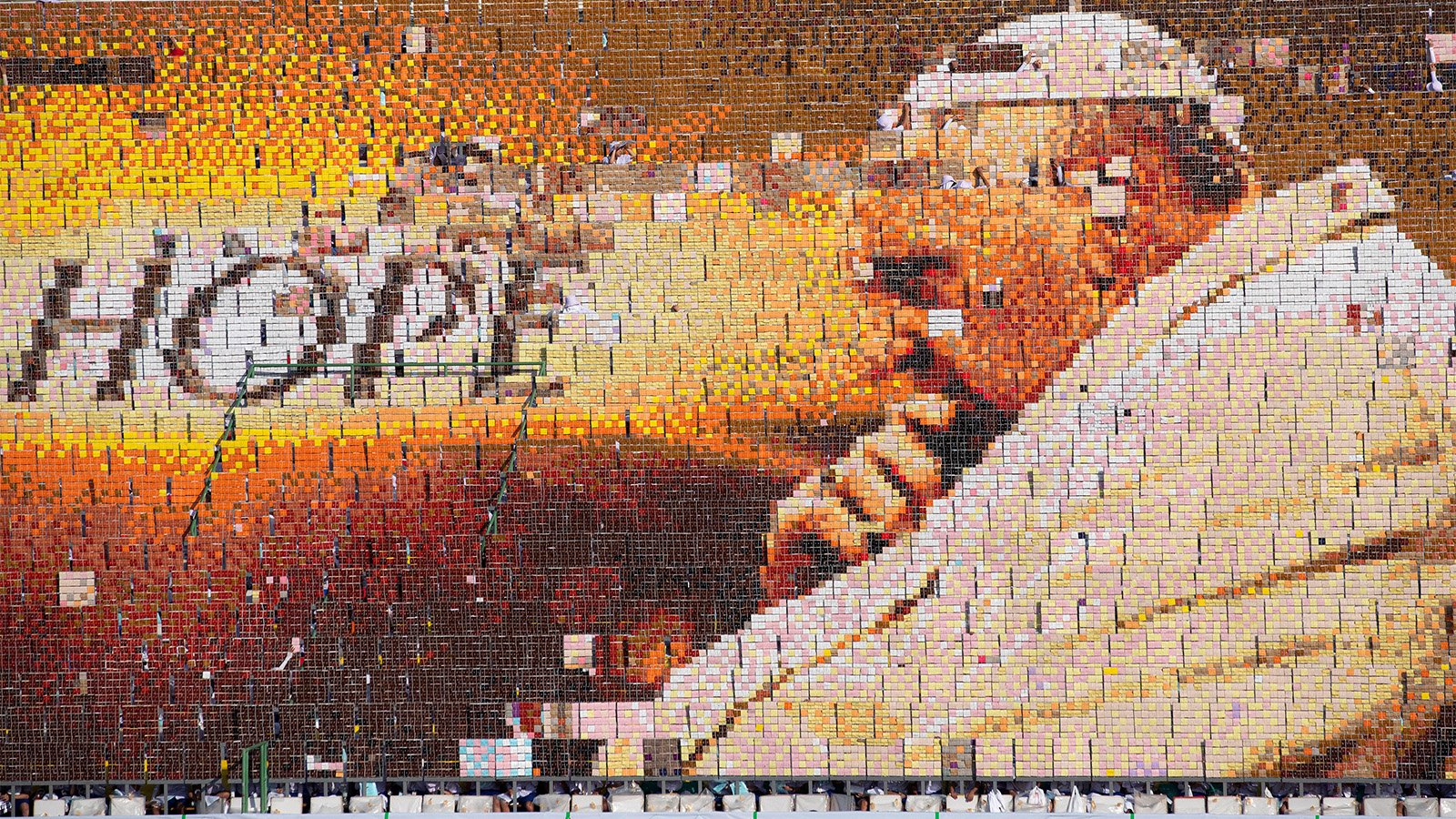 Students practice flipping boards with photos to reveal a full-mosaic portrait of Pope Francis before a Mass at National Stadium in Bangkok on Nov. 21, 2019. (AP Photo/Sakchai Lalit)