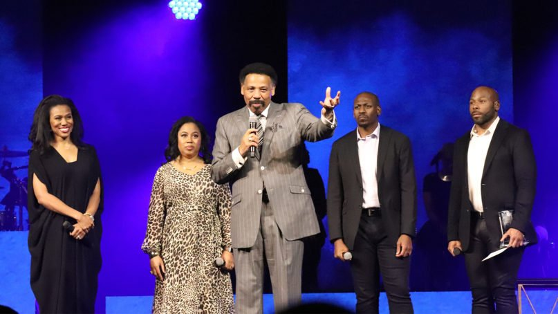 Pastor Tony Evans, center, speaks during the Kingdom Legacy Live event on Friday, Nov. 8, 2019, in Dallas. Evans' children stand behind him. RNS photo by Adelle M. Banks