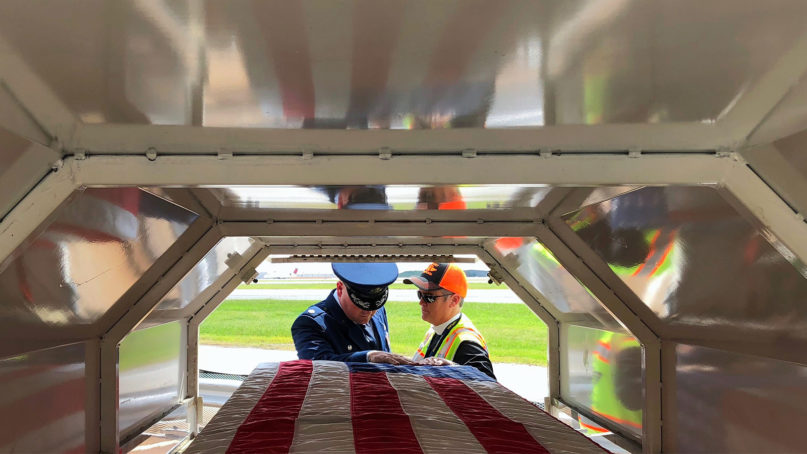 The Rev. Donna Mote, right, a chaplain at Atlanta's Hartsfield-Jackson International Airport, prays over a coffin with a military escort for the life and service of the deceased. They also pray for wisdom and courage for the escort in completing the sacred duty. Photo courtesy of the Rev. Donna Mote