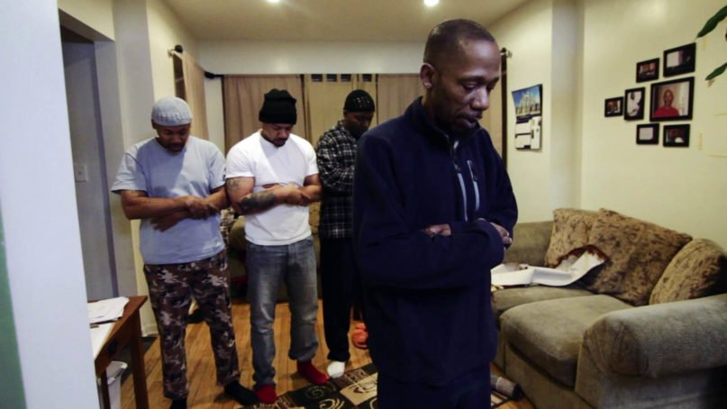 Green ReEntry housemates pray together in the film 'The Honest Struggle.' Photo courtesy of 'The Honest Struggle'