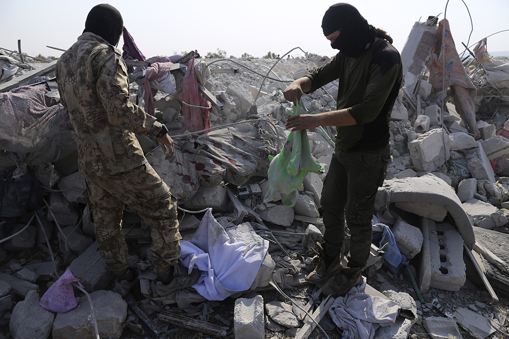 People look at a destroyed compound near the village of Barisha, in Idlib province, Syria, Sunday, Oct. 27, 2019, after an operation by the U.S. military which targeted Abu Bakr al-Baghdadi, the shadowy leader of the Islamic State group. President Donald Trump announced Abu Bakr al-Baghdadi's death after a U.S. military operation in Syria targeted the Islamic State group leader. (AP Photo/Ghaith Alsayed)