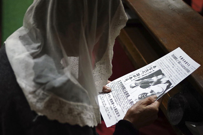A Catholic devotee reads information on Pope Francis's visit during an early morning Mass at the Urakami Cathedral in Nagasaki, southern Japan, on Nov. 17, 2019. Pope Francis will start his first official visit to Japan in Nagasaki, ground zero for the Christian experience in a nation where the Catholic leader once dreamed of living as a missionary. (AP Photo/Eugene Hoshiko)