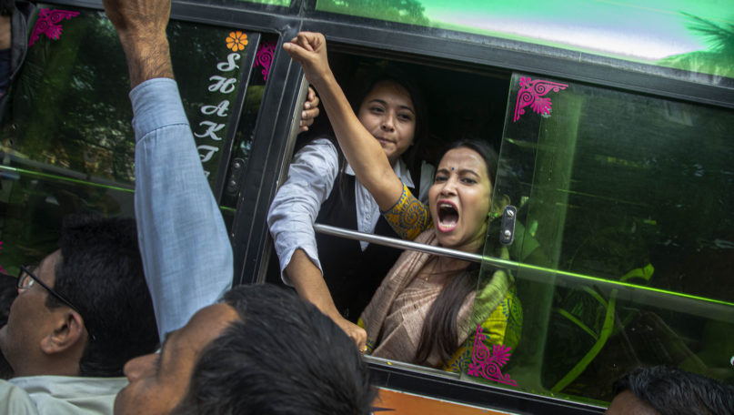 A woman shouts slogans from inside a bus after being detained during a protest against the Citizenship Amendment Act in Gauhati, India, Tuesday, Dec. 17, 2019. Indian student protests that turned into violent clashes with police galvanized opposition nationwide on Tuesday to a new law that provides a path to citizenship for non-Muslim migrants who entered the country illegally from several neighboring countries. (AP Photo/Anupam Nath)