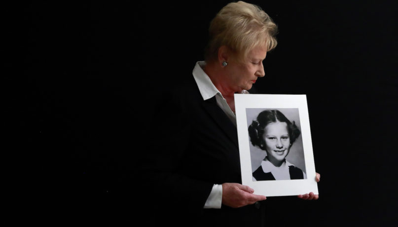 """In this Nov. 20, 2019, photo, Nancy Holling-Lonnecker, 71, poses with a picture taken of her as a young girl, at her home in San Diego. Holling-Lonnecker plans to take advantage of an upcoming three-year window in California that allows people to make claims of sexual abuse no matter how old. Her claim dates back to the 1950s when she says a priest repeatedly raped her in a confession booth beginning when she was 7 years old. """"The survivors coming forward now have been holding on to this horrific experience all of their lives,"""" she said. (AP Photo/Gregory Bull)"""