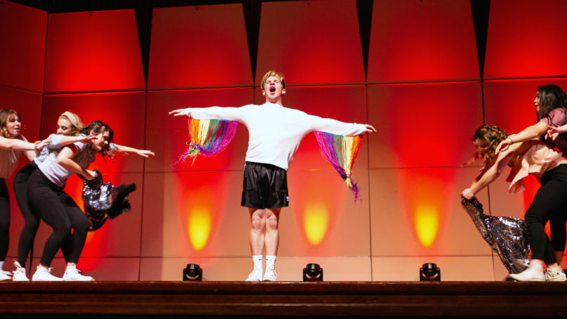 Reid Arthur, center, performs in the lip sync competition at George Fox University on Nov. 16, 2019, in Newberg, Oregon. Backup dancers pulled off his top layer to expose his revealing rainbow-colored streamers. Courtesy photo by Jake Morgan