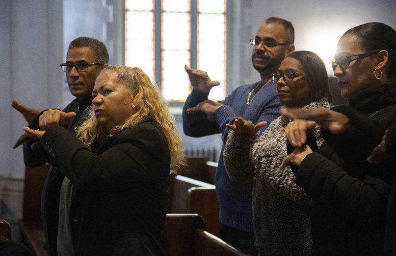 In this Sunday, Dec. 15, 2019, photo, worshippers Carlos Tirado, left, and Lidia Martinez, second from left, sign in response to a sermon at Holyrood Episcopal Church-Iglesia Santa Cruz in New York. Tirado and Martinez, who are deaf, began attending the church last year after seeing the Rev. Maria Santiviago give sermons in sign language. (AP Photo/Jessie Wardarski)