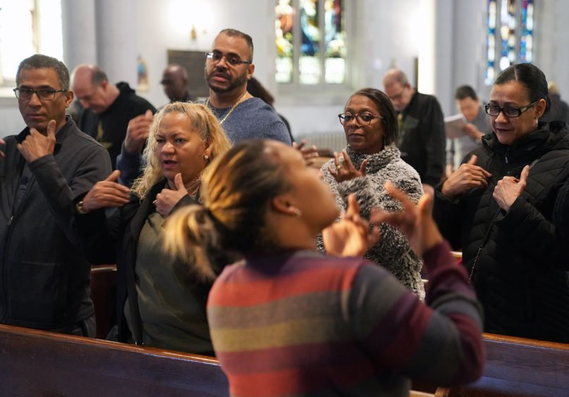 Deaf worshippers sign a hymn while following sign language interpreter Diely Martinez at Holyrood Episcopal Church-Iglesia Santa Cruz in New York City on Dec. 15, 2019. (AP Photo/Emily Leshner)
