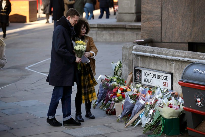 Friends of one of the victims place flowers by London Bridge in London, after an earlier vigil outside the Guildhall, on Dec. 2, 2019. London Bridge reopened to cars and pedestrians Monday, three days after a man previously convicted of terrorism offenses stabbed two people to death and injured three others before being shot dead by police. (AP Photo/Matt Dunham)