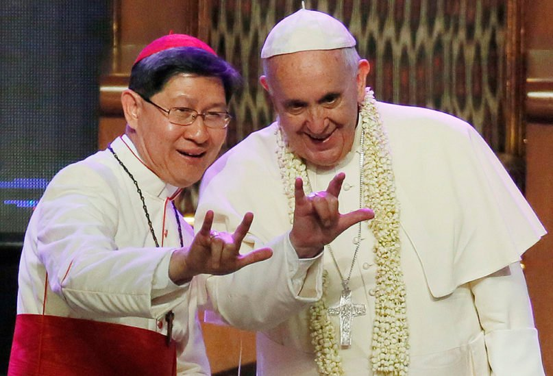 Filipino Cardinal Luis Tagle, left, shows Pope Francis how to give the popular hand sign for
