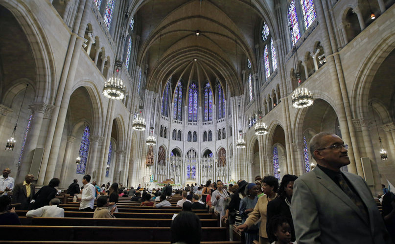 In this July 20, 2014, photo, members of the congregation file out after Sunday morning worship services at Riverside Church in New York. The building is modeled after the 13th century cathedral in Chartres, France. (AP Photo/Kathy Willens)