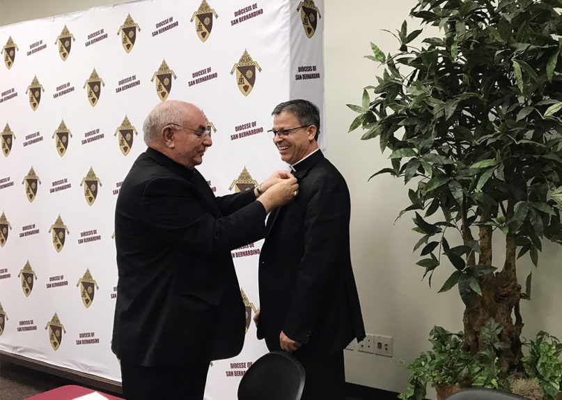 Bishop Gerald Barnes, left, places a pin with the words 'Diocese of San Bernardino' on Bishop Alberto Rojas, an auxiliary bishop of Chicago, who is set to lead the diocese after his anticipated retirement. RNS photo by Alejandra Molina