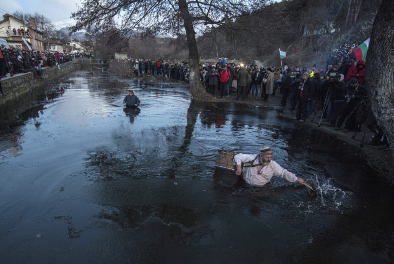 A drummer breaks ice prior to the Epiphany ritual, in Kalofer, Bulgaria, Monday, Jan. 6, 2020. Thousands of Orthodox Christian worshippers plunged into the icy waters of rivers and lakes across Bulgaria on Monday to retrieve crucifixes tossed by priests in ceremonies commemorating the baptism of Jesus Christ. In the mountain city of Kalofer, in central Bulgaria, dozens of men dressed in white embroidered shirts waded into the frigid Tundzha River waving national flags and singing folk songs. (AP Photo)