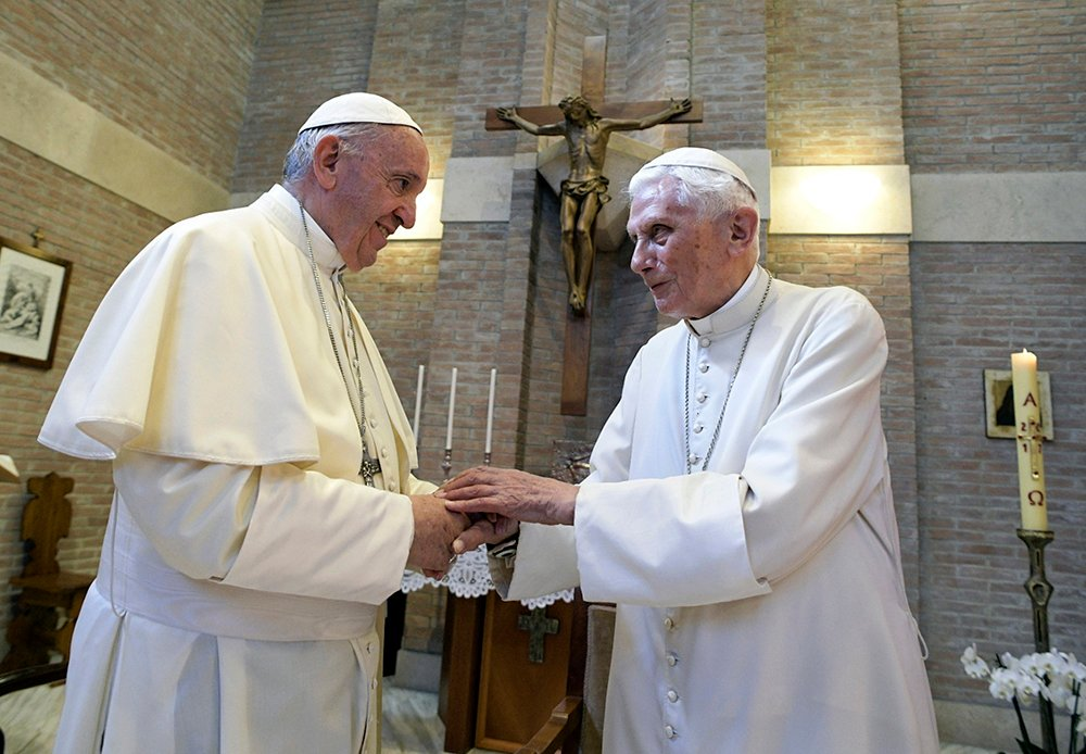 In this June 28, 2017, file photo, Pope Francis, left, and Pope Benedict XVI meet each other on the occasion of the elevation of five new cardinals at the Vatican. (L'Osservatore Romano/Pool photo via AP, File)