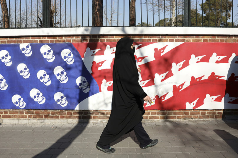A mourner walks back from a funeral ceremony for Iranian Gen. Qassem Soleimani and his comrades, who were killed in Iraq in a U.S. drone attack, passing graffiti on the wall of the former U.S. Embassy in Tehran, Iran, Monday, Jan. 6, 2020. Funeral ceremonies for Soleimani drew a crowd said by police to be in the millions, on Monday in Tehran, where his replacement vowed to take revenge. (AP Photo/Vahid Salemi)