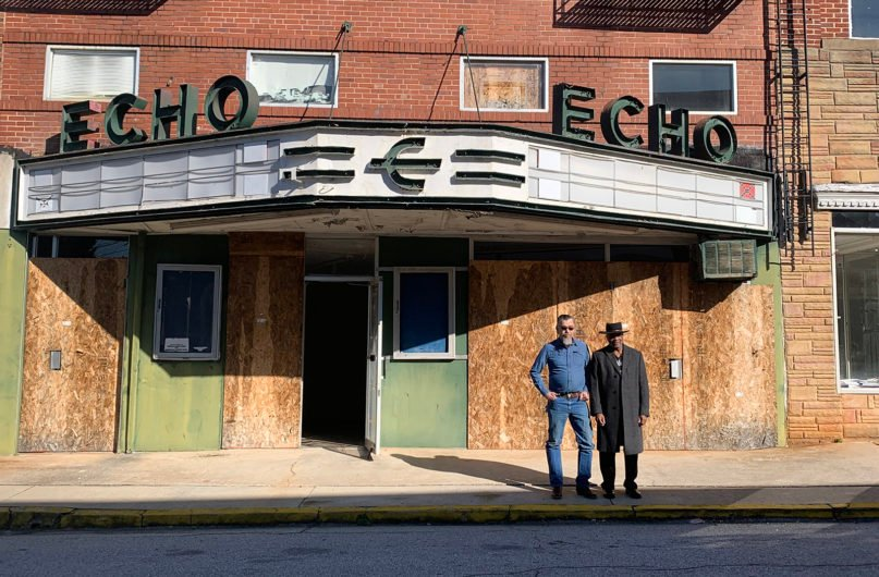 Michael Burden, left, and the Rev. David Kennedy stand in front of Echo Theater in Laurens, South Carolina. The theater formerly housed the Redneck Shop, a white supremacist store and meeting place, which closed in 2012. Photo courtesy of 101 Studios