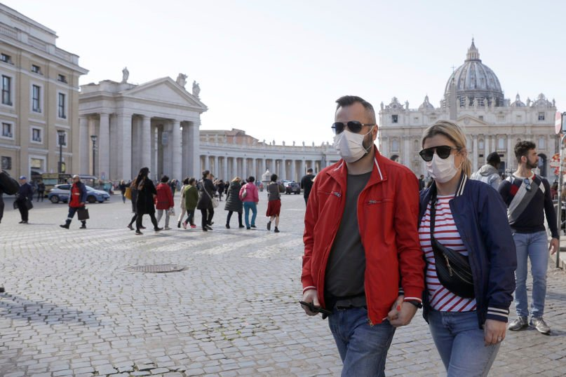 A couple wearing face masks stroll outside St. Peter's Square, at the Vatican, on Feb. 27, 2020. Clusters of coronavirus outbreaks in northern Italy have stoked fears throughout Italy and Europe. (AP Photo/Gregorio Borgia)