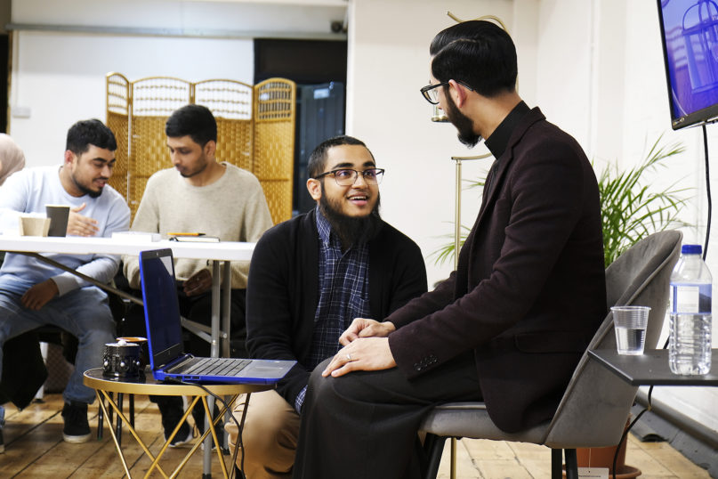 Faith community co-founders Adel Chowdhury, center, and Imam Shabbir Hassan, right, chat during a break in a session Jan. 27, 2020, in the group's new permanent space in London. RNS photo by Aysha Khan