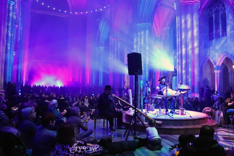 """People sit on the floor of the Washington National Cathedral nave around Earth Music Effects musicians, Monday, Feb. 10, 2020, for a """"Space, Light and Sound"""" show as part of the Seeing Deeper Week at the cathedral in Washington. RNS photo by Adelle M. Banks"""