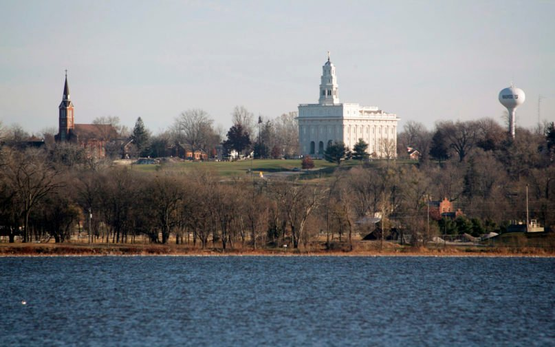 The city of Nauvoo, Illinois, with The Church of Jesus Christ of Latter-day Saints Nauvoo Illinois Temple, center, and the Sts. Peter and Paul Catholic Church, left, is seen from across the Mississippi River in Montrose, Iowa, Nov. 29, 2007. The town is one of the most important towns in the history of the Mormon church. (AP Photo/John Gaines)