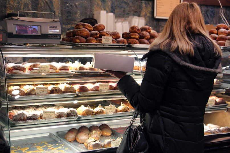A customer selects paczki from displays at Kolatek's Bakery, Tuesday morning, Feb. 25, 2020, in Chicago. RNS photo by Emily McFarlan Miller
