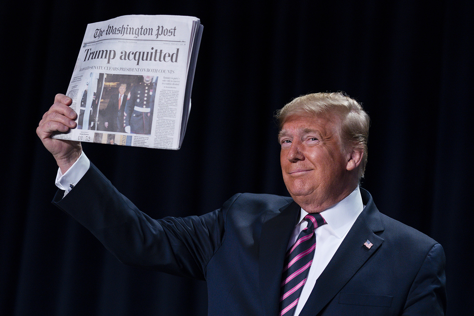 """President Donald Trump holds up a newspaper with the headline that reads """"Trump acquitted"""" during the 68th annual National Prayer Breakfast, at the Washington Hilton, on Feb. 6, 2020, in Washington. (AP Photo/ Evan Vucci)"""