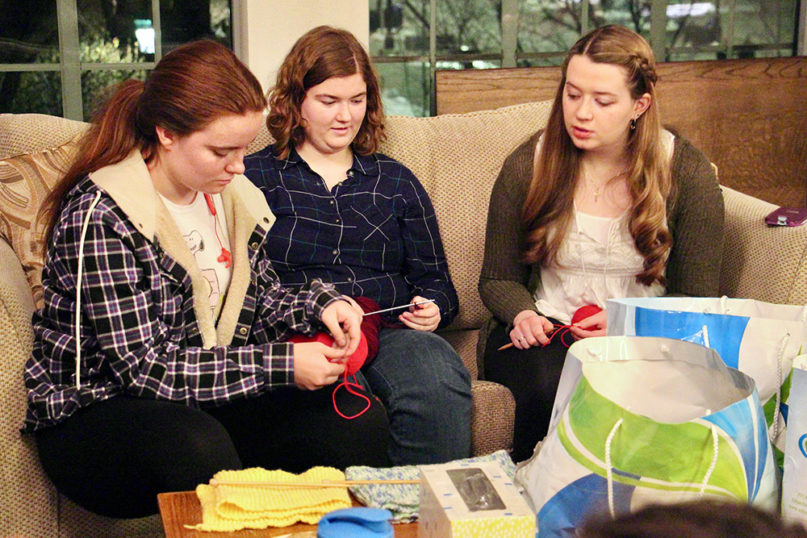 Senior Kara Fontana, right, teaches freshmen Emma Brown, left, and Allyson Mills, center, how to knit during Knitting Together, on Feb. 3, 2020, at Pres House, the campus ministry of the Presbyterian Church (U.S.A.) at the University of Wisconsin-Madison. RNS photo by Emily McFarlan Miller