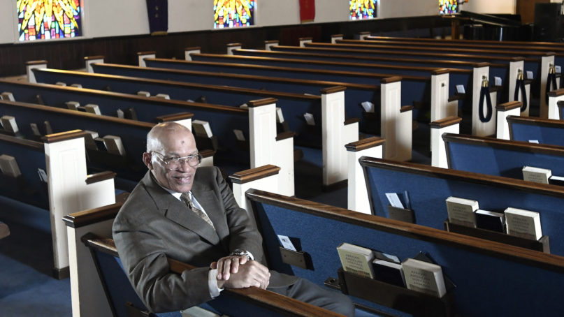 """The Rev. Alvin J. Gwynn Sr., of Friendship Baptist Church in Baltimore, sits in his church's sanctuary March 19, 2020. He bucked the cancellation trend by holding services the previous Sunday. But attendance was down by about 50%, and Gwynn said the day's offering netted about $5,000 compared with a normal intake of about $15,000. """"It cuts into our ministry,"""" he said. """"If this keeps up, we can't fund all our outreach to help other people."""" (AP Photo/Steve Ruark)"""