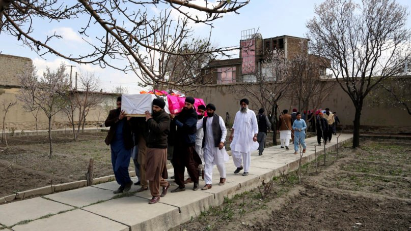 Afghan Sikh men carry coffins of their beloved ones during a funeral procession for those who were killed on Wednesday by a lone Islamic State gunman, rampaged through a Sikh house of worship, in Kabul, Afghanistan, Thursday, March 26, 2020. An explosive device disrupted Thursday's funeral service for 25 members of Afghanistan's Sikh minority community, killed in an attack by the Islamic State group on their house of worship in the heart of the capital. (AP Photo/Tamana Sarwary)