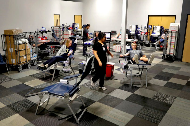 People donate blood at a temporary blood bank set up in a church's fellowship hall March 24, 2020, in Tempe, Arizona. Schools and businesses that typically host blood drives are temporarily closed due to precautionary measures in place to reduce the spread of the COVID-19 coronavirus, leading to extremely low levels of blood availability throughout the country. (AP Photo/Matt York)