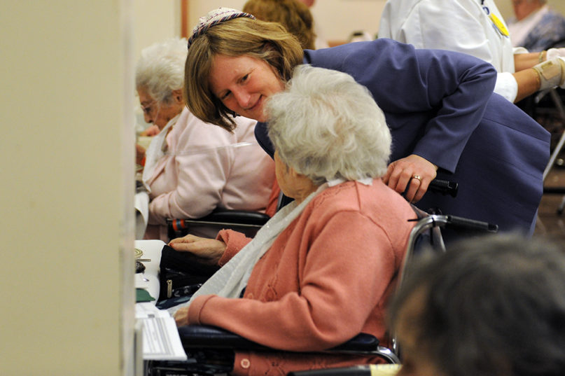 Rabbi Sara Paasche-Orlow talks with a resident at a Hebrew SeniorLife facility in Fall 2019, in Massachusetts. Photo courtesy of Hebrew SeniorLife