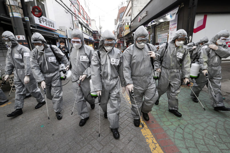 Army soldiers wearing protective suits spray disinfectant as a precaution against the new coronavirus at a shopping street in Seoul, South Korea, on March 4, 2020. The coronavirus epidemic shifted increasingly westward toward the Middle East, Europe and the United States on Tuesday, with governments taking emergency steps to ease shortages of masks and other supplies for front-line doctors and nurses. (AP Photo/Ahn Young-joon)