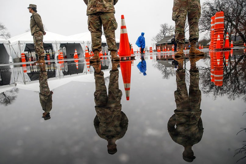"""National Guard personnel stand at attention as they wait for patients to arrive at a COVID-19 coronavirus testing facility at Glen Island Park, Friday, March 13, 2020, in New Rochelle, N.Y. State officials have set up a """"containment area"""" in the New York City suburb, where schools and houses of worship are closed within a 1-mile radius of a point near a synagogue where an infected person with coronavirus had attended events. State officials stress it is not a lockdown. The vast majority of people recover from the new coronavirus. According to the World  Health Organization, most people recover in about two to six weeks, depending on the severity of the illness. (AP Photo/John Minchillo)"""