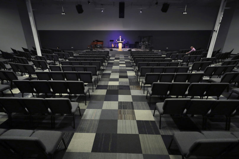 Josh Kellso, a pastor at Grace Bible Church, delivers a sermon via livestream for virtual attendees from an empty sanctuary March 22, 2020, in Tempe, Arizona. (AP Photo/Matt York)