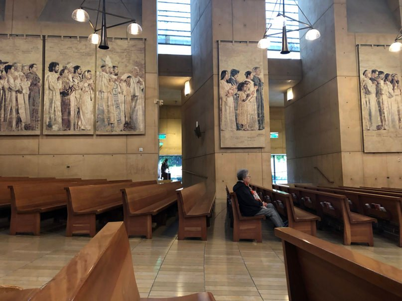 A woman sits alone in her pew during Mass at the Cathedral of Our Lady of the Angels, Sunday, March 15, 2020, in Los Angeles. Photo by Hayley Smith