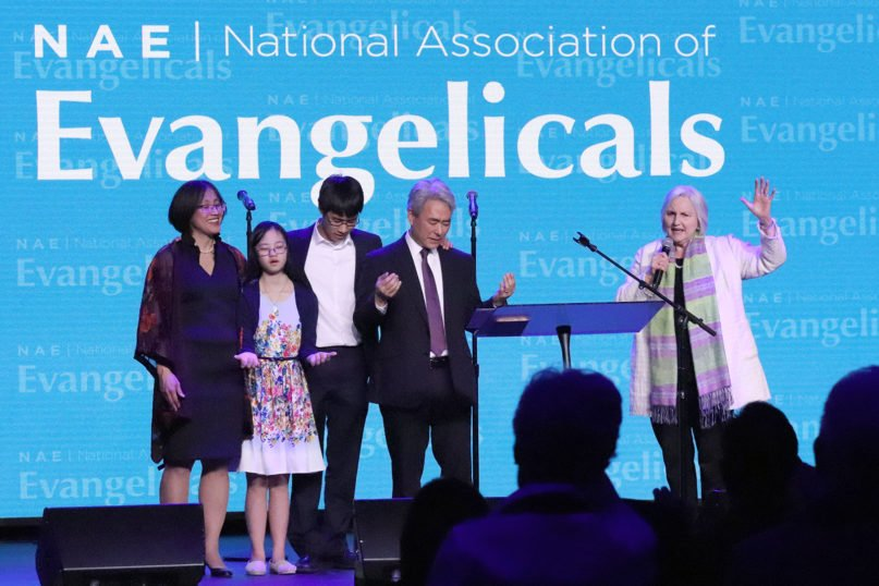 Jo Anne Lyon, right, prays over the Rev. Walter Kim, center, and his family during Kim's inauguration as the new president of the National Association of Evangelicals at the Capital Turnaround venue in Washington, Wed., March 4, 2020. RNS photo by Adelle M. Banks