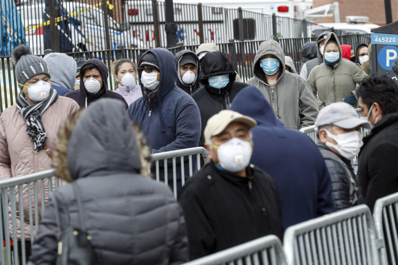 Patients wear face masks as they wait in line for a COVID-19 test at Elmhurst Hospital Center on March 25, 2020, in New York. Gov. Andrew Cuomo sounded his most dire warning yet about the coronavirus pandemic Tuesday, saying the infection rate in New York is accelerating and the state could be as close as two weeks away from a crisis that sees 40,000 people in intensive care. Such a surge would overwhelm hospitals, which now have just 3,000 intensive care unit beds statewide. (AP Photo/John Minchillo)