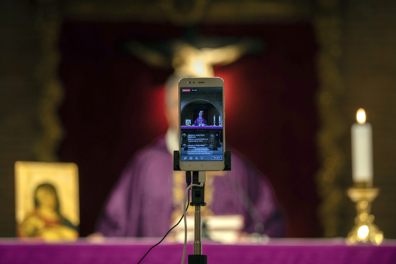 Catholic priest Jesus Higueras from the Santa Maria de Cana parish is seen on a smartphone during a livestreamed Mass in Pozuelo de Alarcon, on the outskirts of Madrid, on March 15, 2020. (AP Photo/Bernat Armangue)