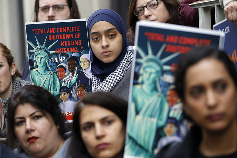 Demonstrators listen to speakers during a rally outside the U.S. 4th Circuit Court of Appeals Tuesday Jan 28, 2020, in Richmond, Va.  President Donald Trump's travel ban on travelers from predominantly Muslim countries is going back before a federal appeals court. (AP Photo/Steve Helber)