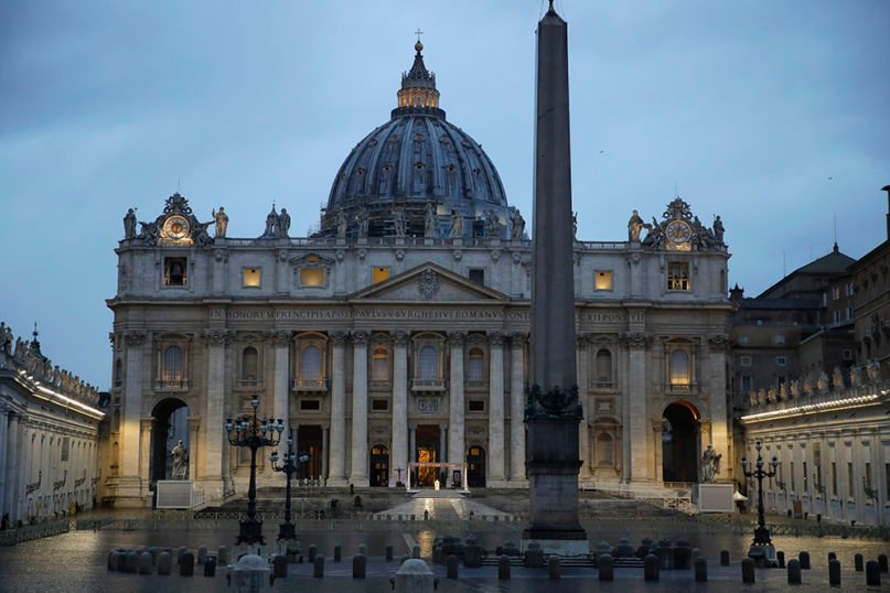 """Pope Francis, white figure standing alone at center, delivers an Urbi et Orbi blessing from the empty St. Peter's Square, at the Vatican, on March 27, 2020. Francis has likened the coronavirus pandemic to a storm laying bare illusions that people can be self-sufficient and instead finds """"all of us fragile and disoriented"""" and needing each other's help and comfort. (AP Photo/Alessandra Tarantino)"""