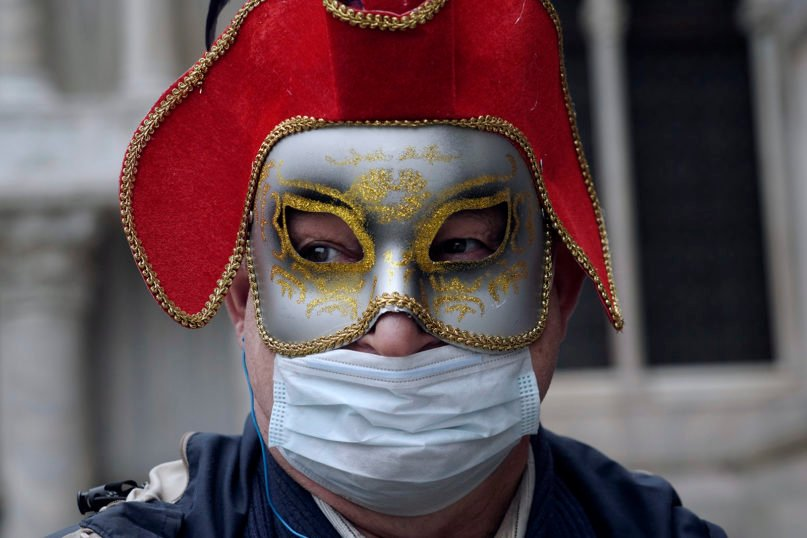 A tourist dons both a Carnevale mask and a protective face mask as he visits St. Mark's Square in Venice, Italy, on Feb. 25, 2020. Italy has been scrambling to check the spread of Europe's first major outbreak of the new viral disease amid rapidly rising numbers of infections and calling off the popular Venice Carnevale and closing tourist attractions. (AP Photo/Renata Brito)
