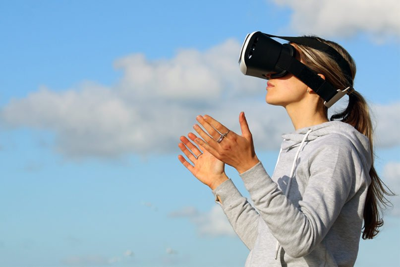A woman uses a virtual reality headset outdoors. Photo courtesy of Pexels/Creative Commons