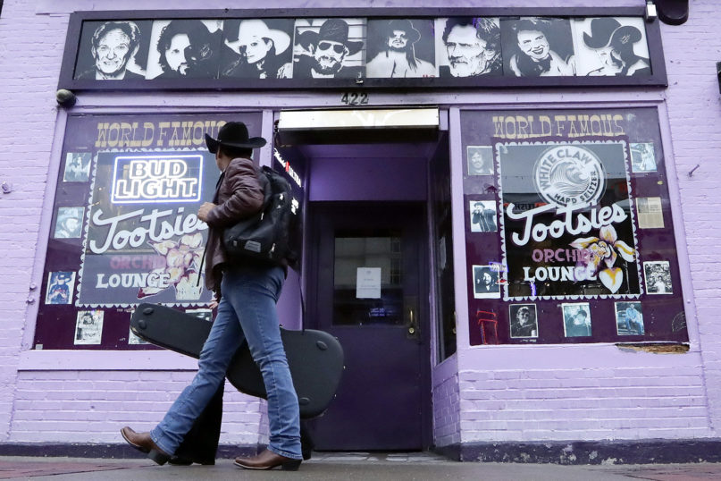 A man walks by Tootsie's Orchid Lounge, closed because of the coronavirus, Monday, March 16, 2020, in Nashville, Tenn. Nashville Mayor John Cooper has called for bars on Broadway and throughout the county to close until further notice. (AP Photo/Mark Humphrey)